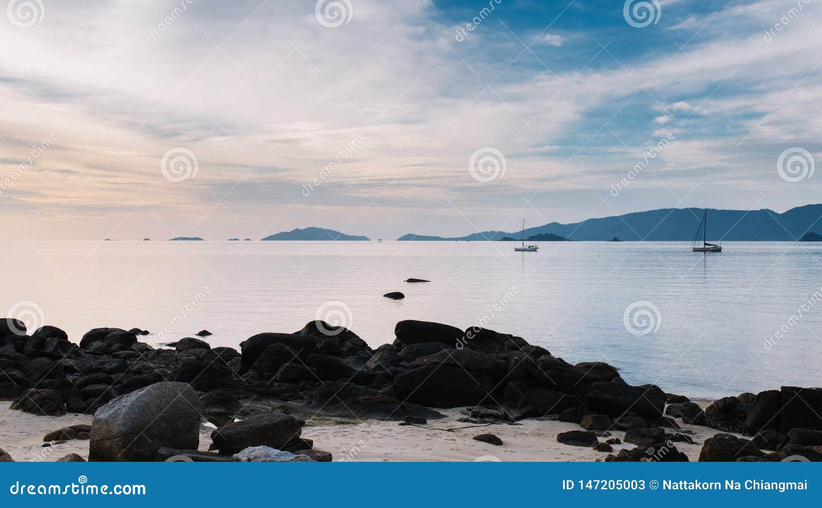 Piękny widok zmierzch przy plaży i jachtu cumowaniem