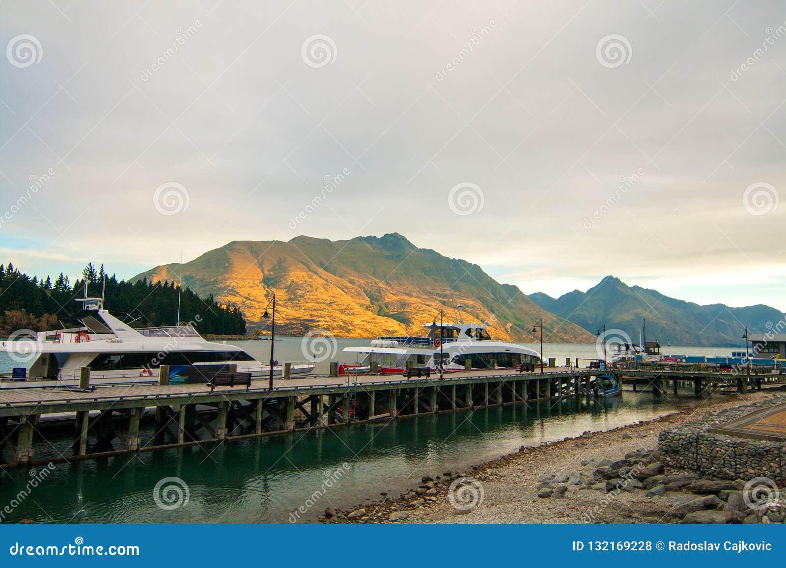 Piękny złoty zmierzch zaświeca na górach, luksusowe łodzie dokuje na jeziornym Wakatipu, Queenstown nabrzeże