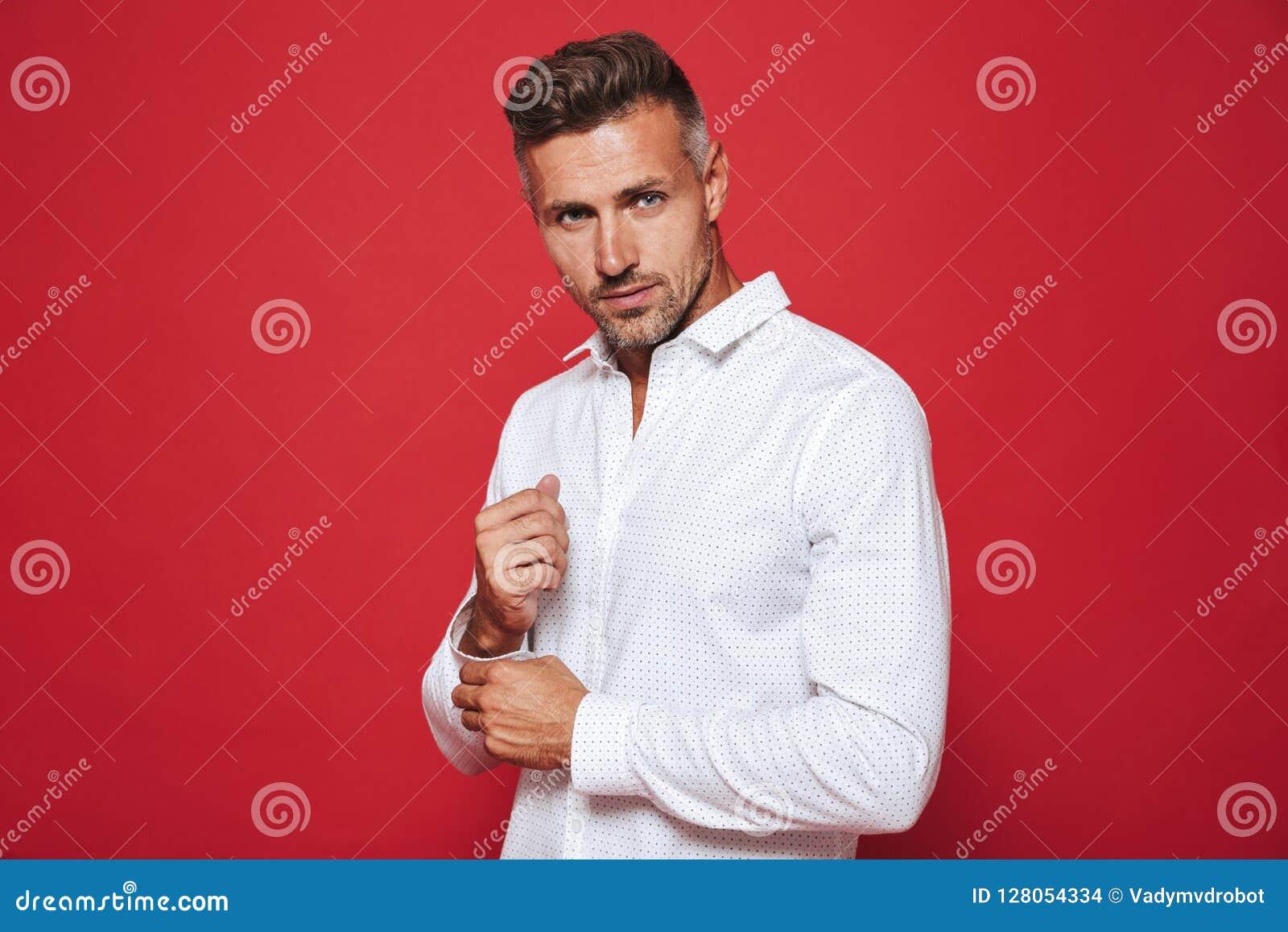 Piękny zarośnięty mężczyzna 30s w biały koszulowy patrzeć na kamerze, iso