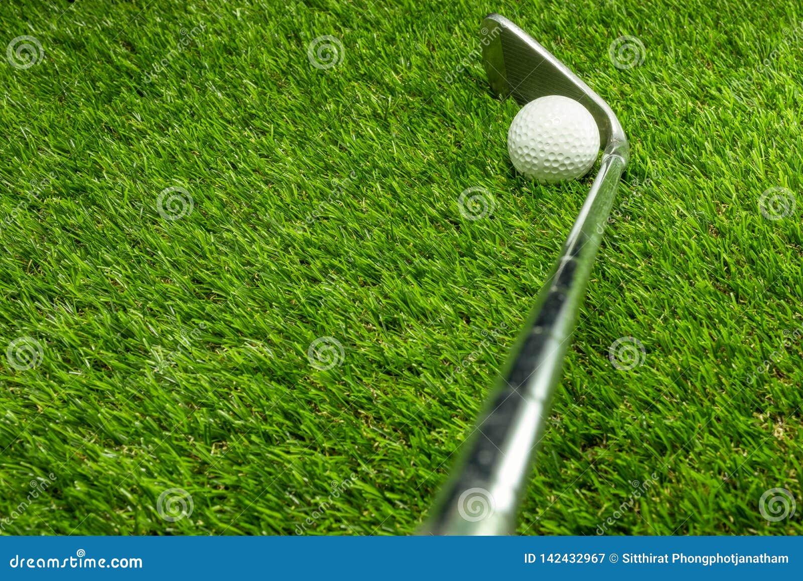 Piłka golfowa i kij golfowy na trawie