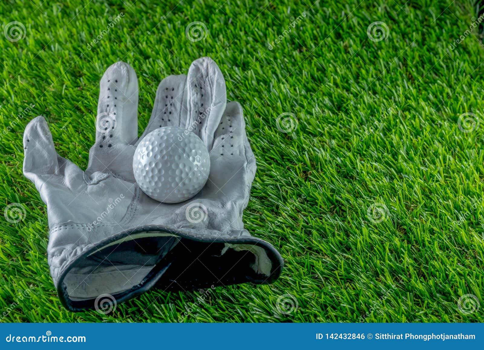 Piłka golfowa i rękawiczka na trawie