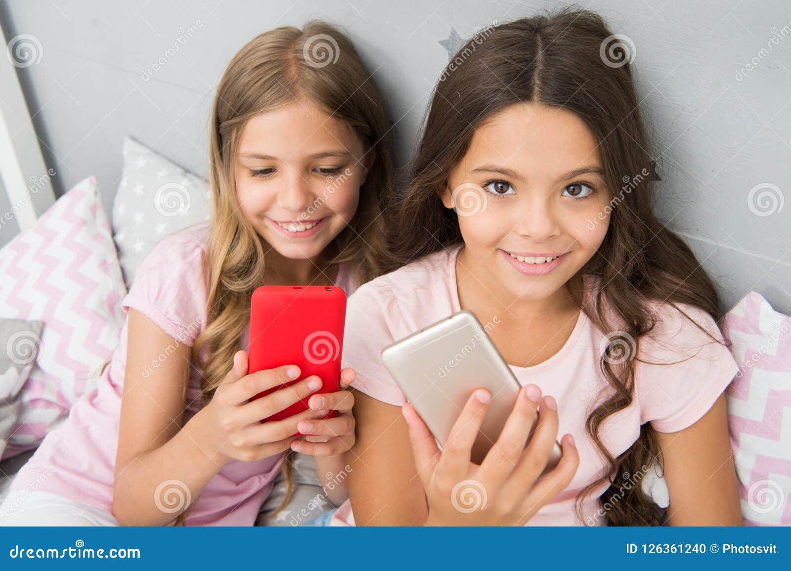 Piżamy przyjęcia pojęcie Dziewczęcego czasu wolnego szczęśliwy dzieciństwo Dziewczyny długie włosy z smartphones use nowożytną te