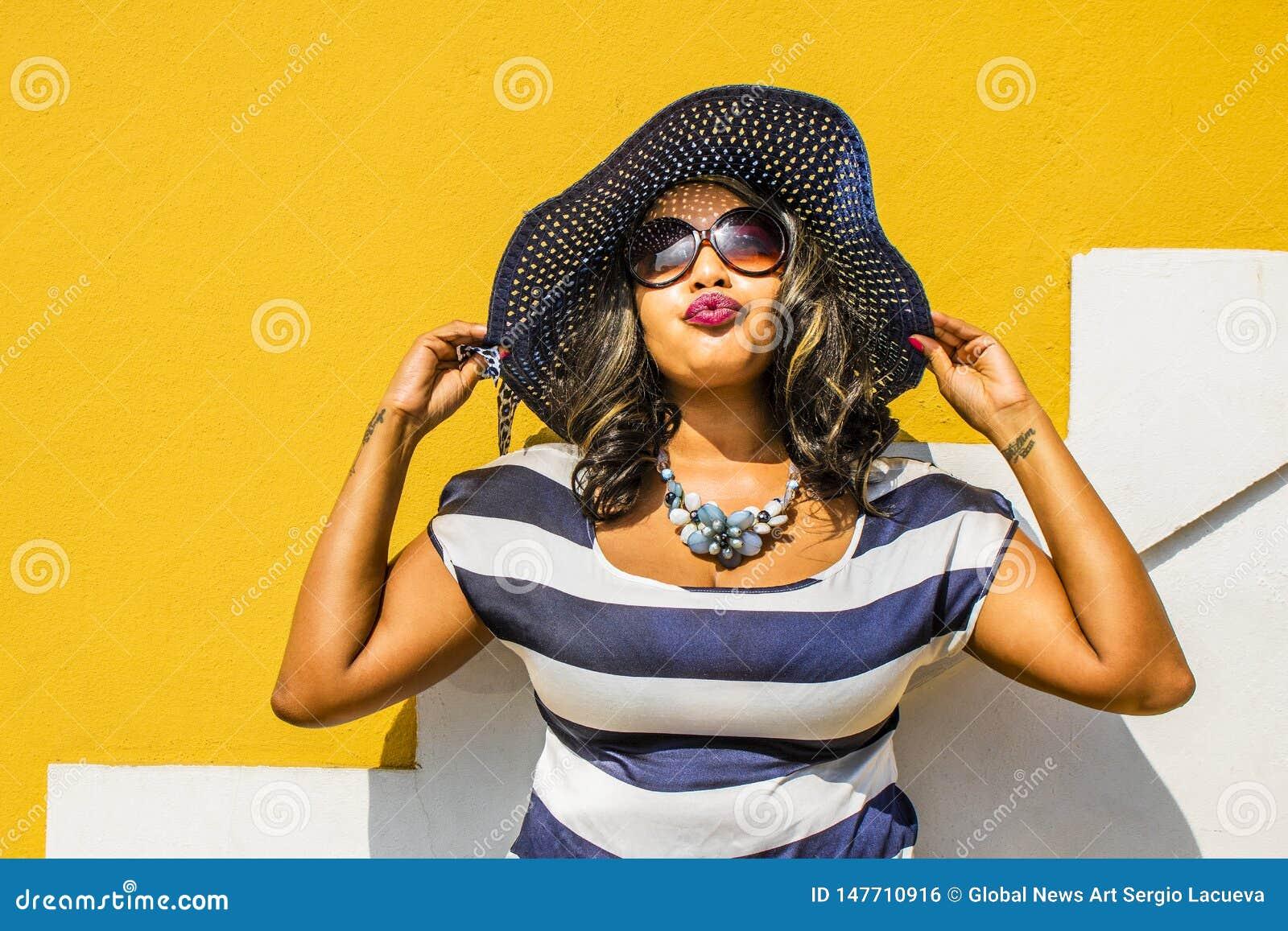 Pi?kna Afryka?ska kobieta w b??kitnej i bia?ej pasiastej smokingowej modelacji przed tradycyjnym bo domem z kolor ?