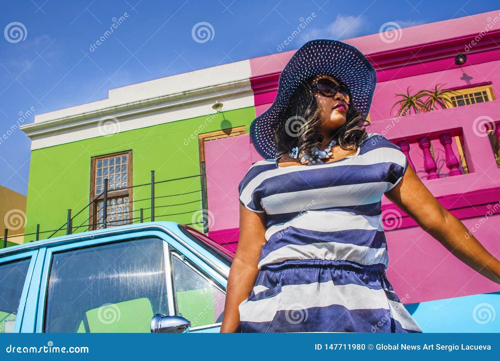 Pi?kna Afryka?ska kobieta w bielu i b??kitnym paskowa? sukni? przed rocznika Ford Cortina tradycyjnymi domami bo i, C