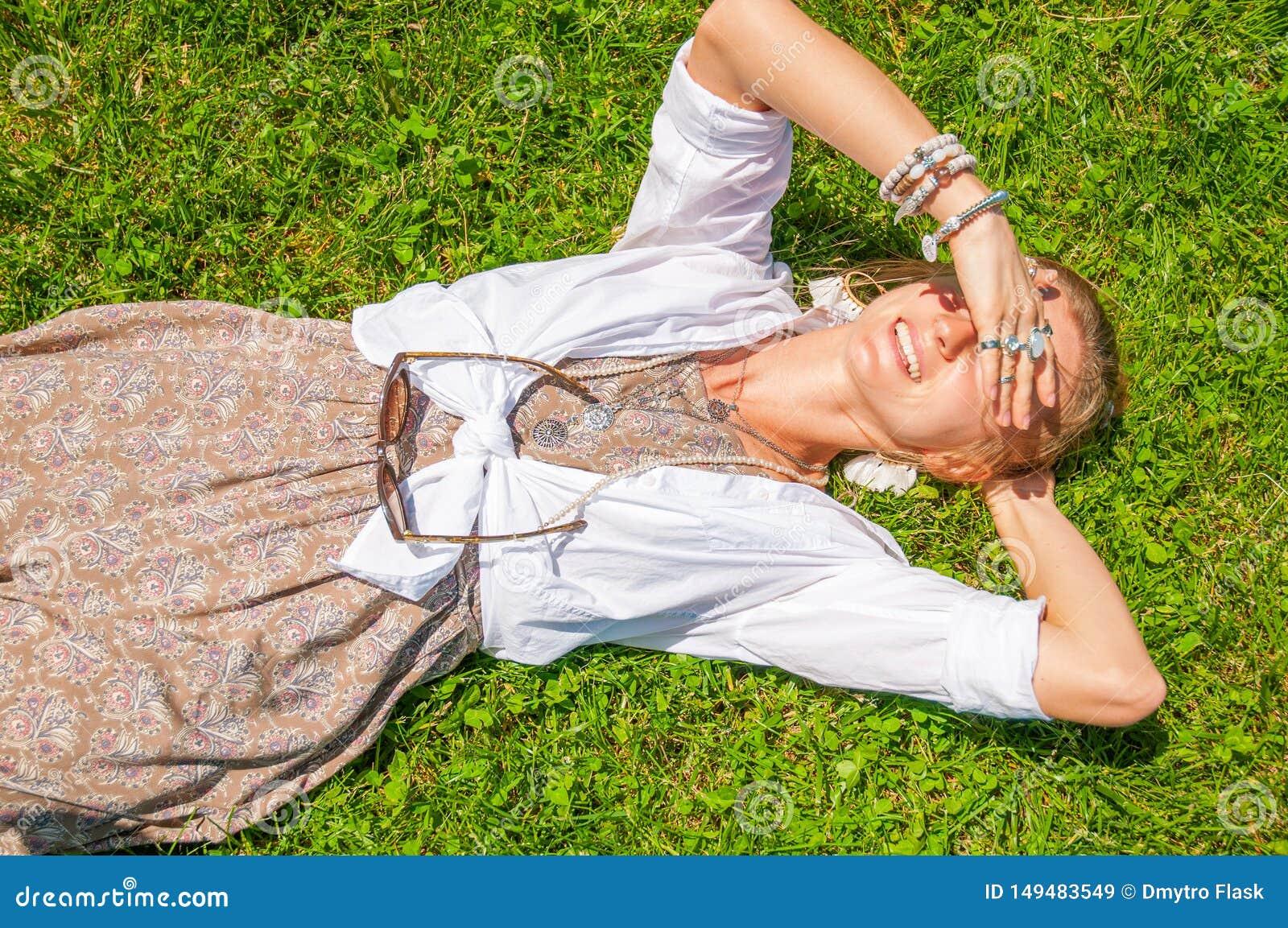 Pi?kna boho stylu kobieta z mn?stwo akcesoriami k?ama na zielonej trawie Szcz??liwy mometn