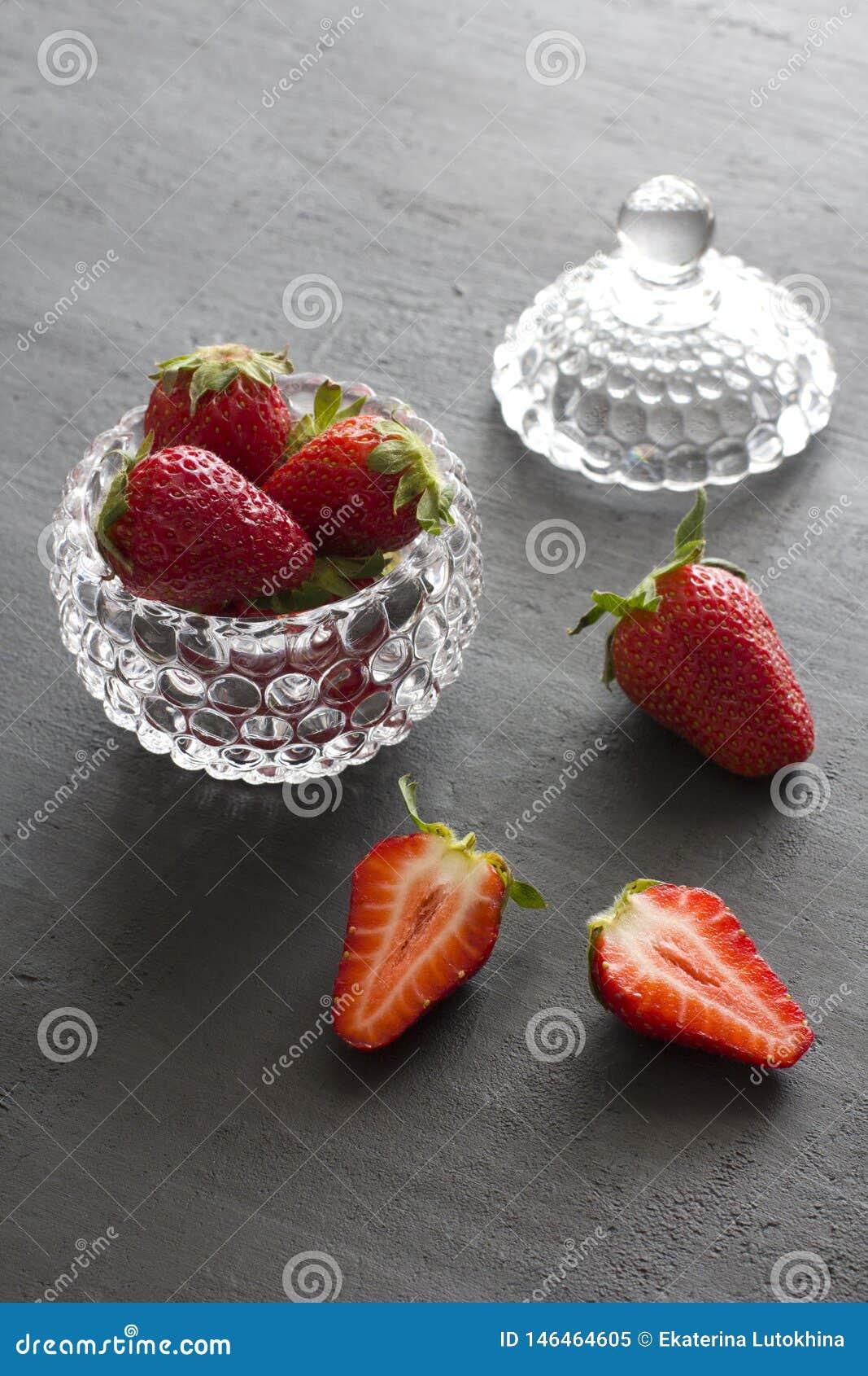 Pi?kna czerwona truskawka w szklanym round pucharze Truskawki na czarnym zmroku betonu tle Wie?niaka styl horyzontalny
