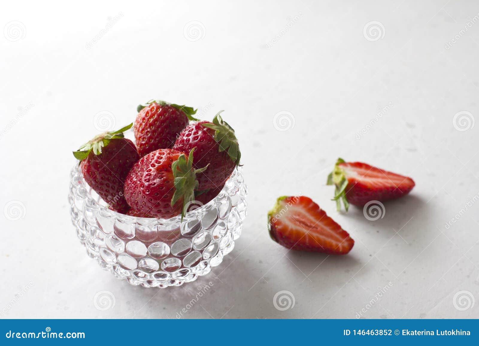 Pi?kna czerwona truskawka w szklanym round pucharze Truskawki na lekkim bielu betonu tle Wie?niaka styl R?ni?te truskawki,