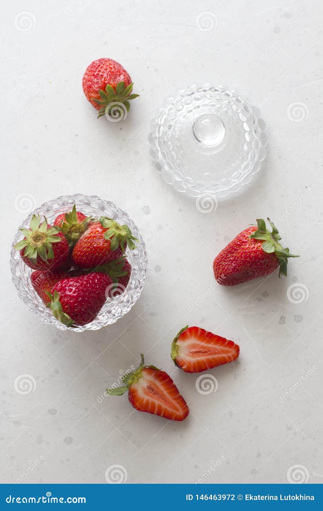 Pi?kna czerwona truskawka w szklanym round pucharze Zamkni?tym w g?r? Truskawki na lekkim bielu betonu tle Wie?niaka styl ci?cie