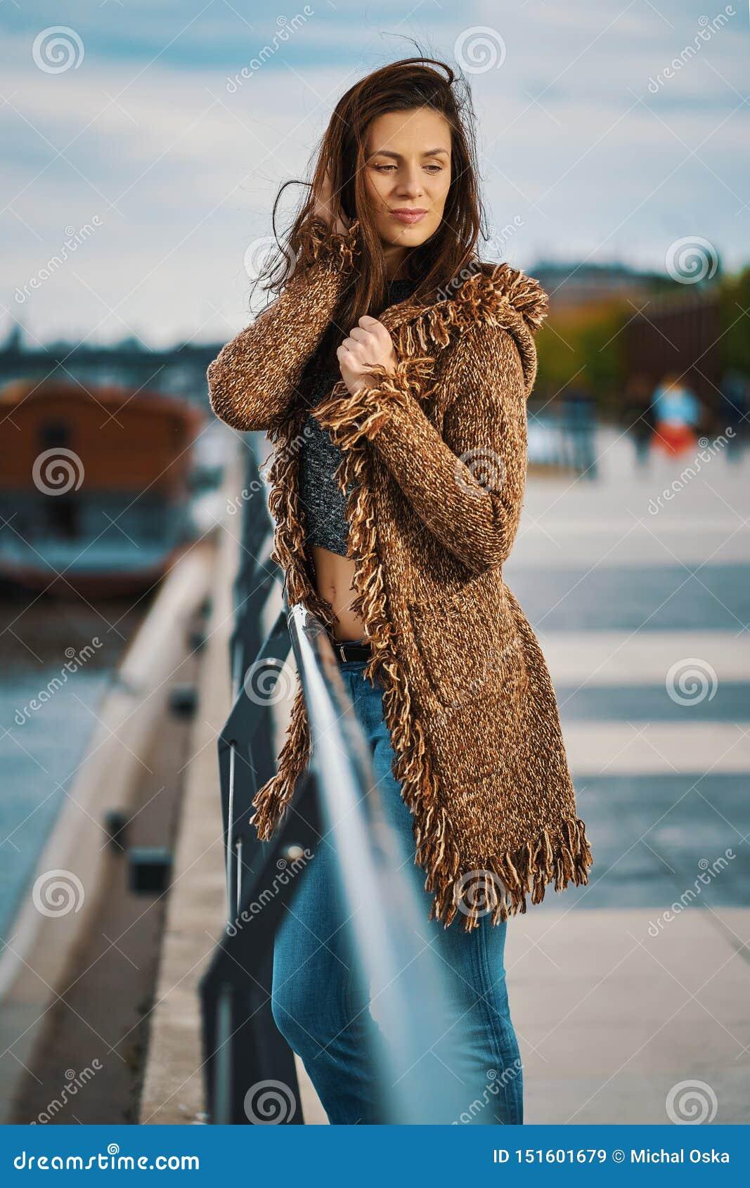 Pi?kna m?oda kobieta pozuje na deptaku przy rzek? w mie?cie