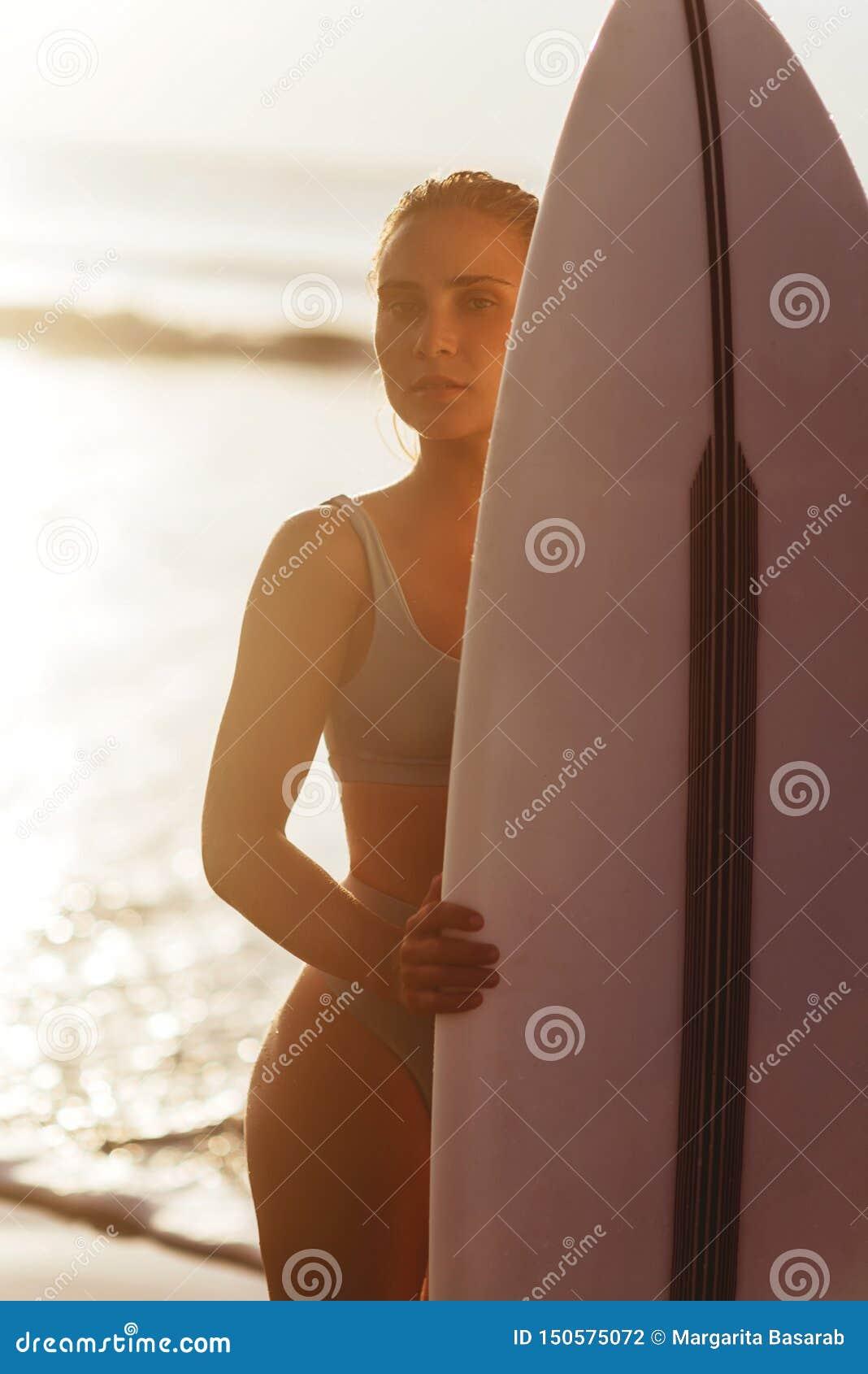 Pi?kna seksowna surfingowiec dziewczyna na pla?y przy zmierzchem