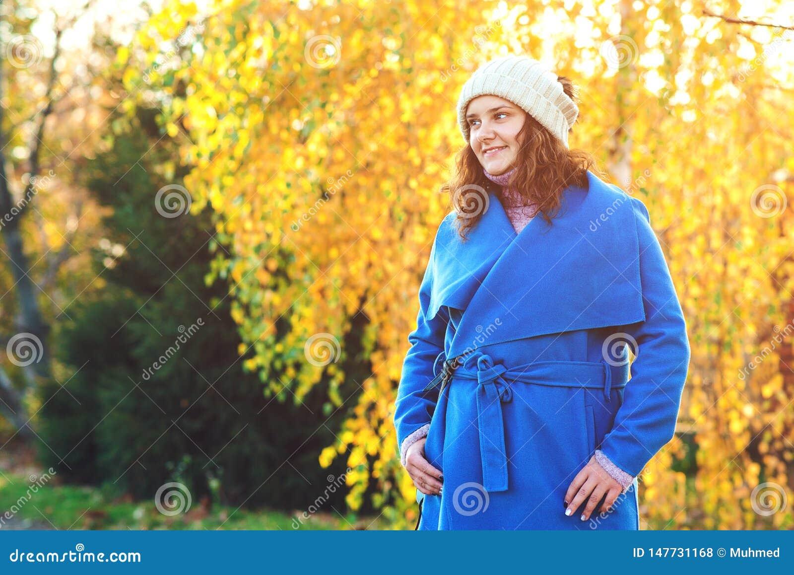 Pi?kny Jesie? pi?kna Kobieta fasonuje kobiety Młoda kobieta ubierał w błękitnym żakiecie i ciepłym kapeluszu chodzi w jesień park