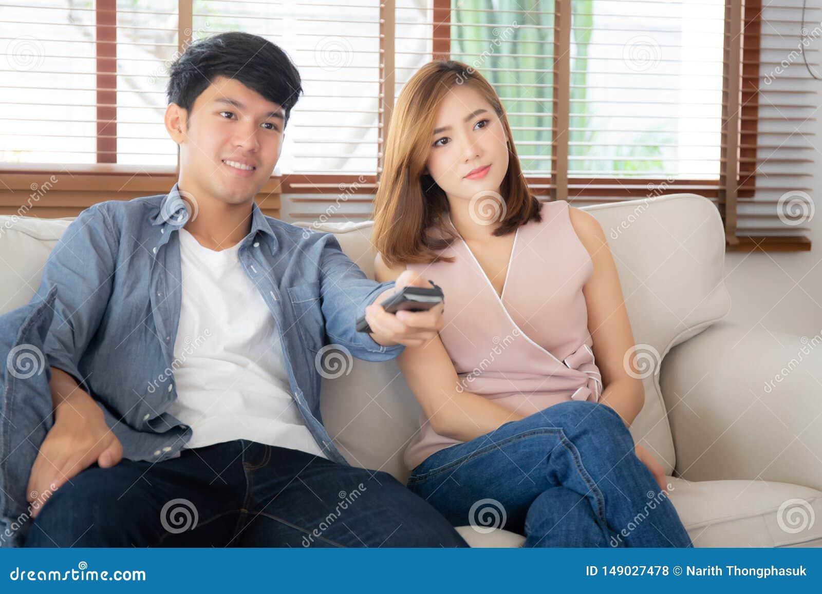 Pi?kny m?ody azjatykci pary mienia pilot, dopatrywanie tv i wideo leje si? na kanapie z relaksujemy i szcz??liwy