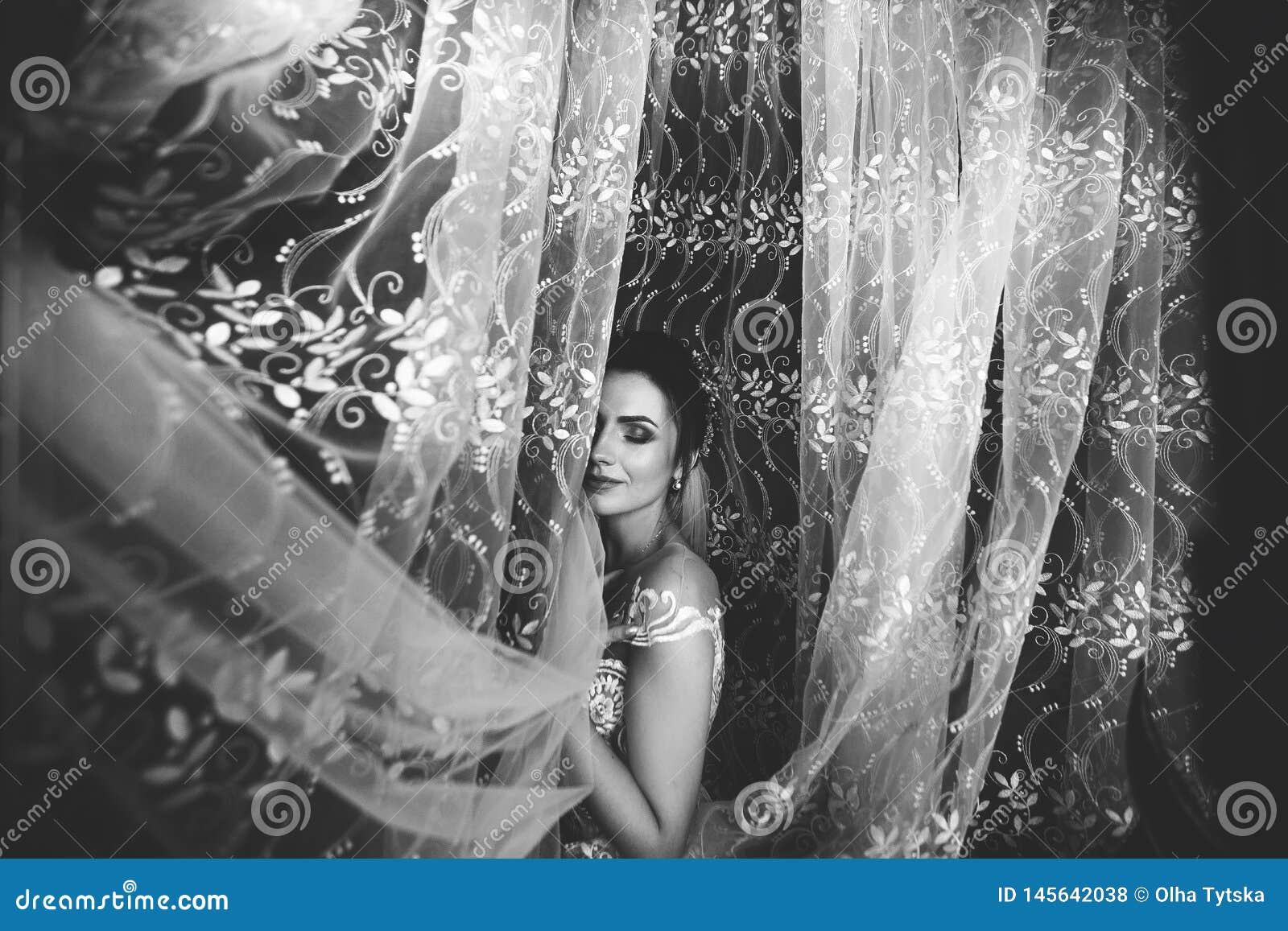 Pi?kny panna m?oda styl ?lubny dziewczyna stojak w luksusowej ?lubnej sukni blisko okno czarny white