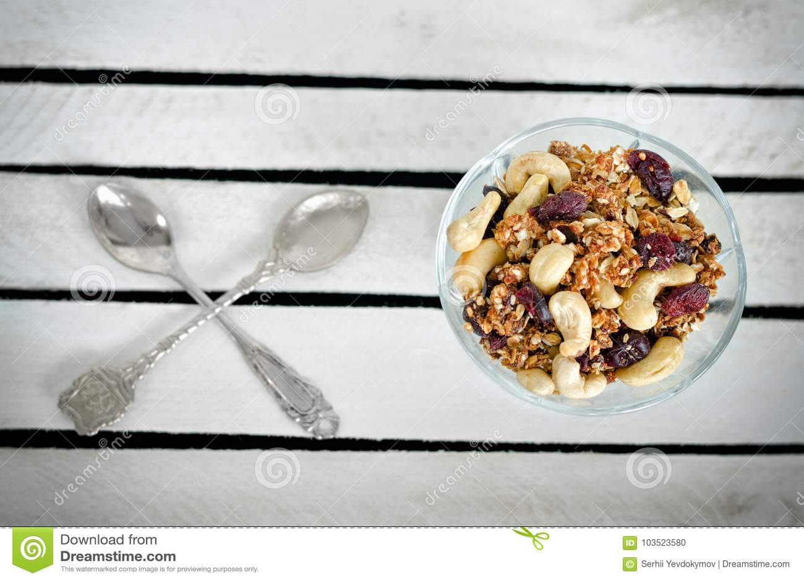 Piala με το granola και δύο διασχισμένα κουτάλια σε ένα άσπρο ξύλινο κιβώτιο