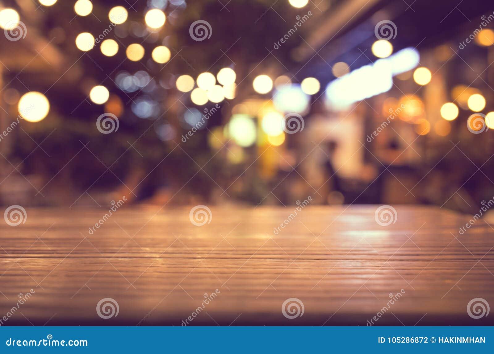 Piano dappoggio di legno con sfuocatura di illuminazione nel