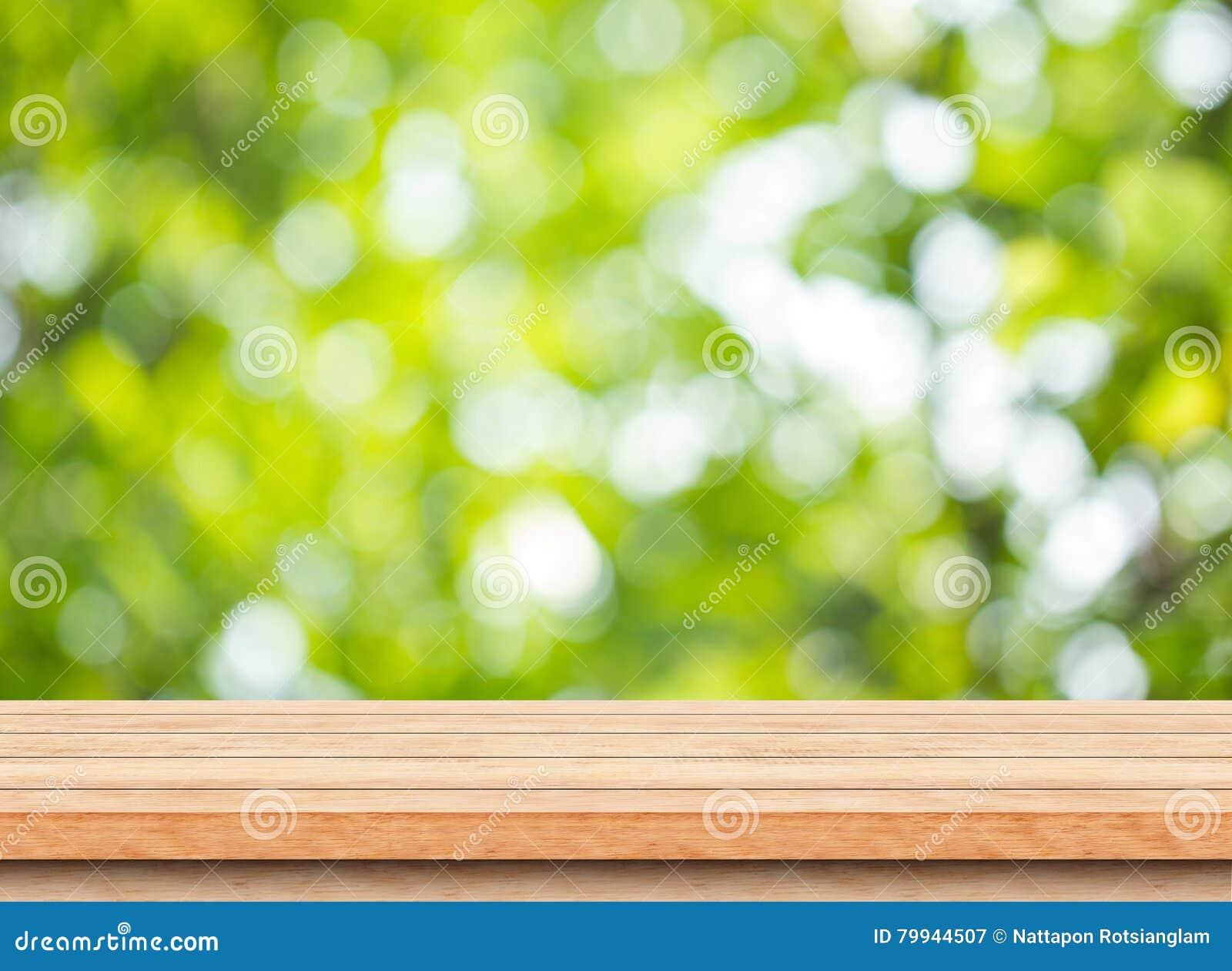 Piano d appoggio di legno marrone vuoto con il fondo del bokeh dell albero di verde della sfuocatura