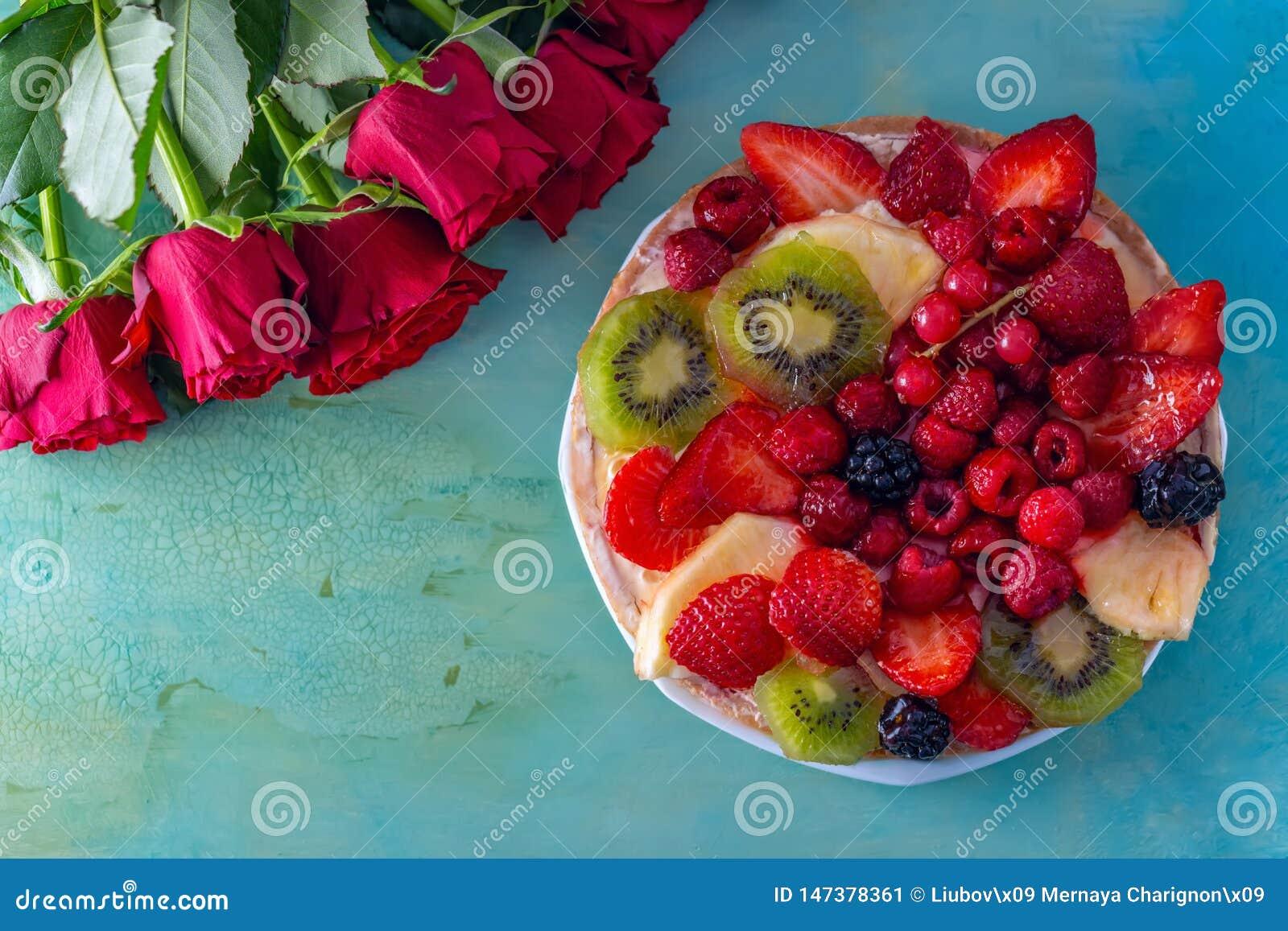 Piano-disposizione delle rose rosse dei fiori e di bello dolce dolce delizioso con le bacche su un fondo verde Cartolina d auguri
