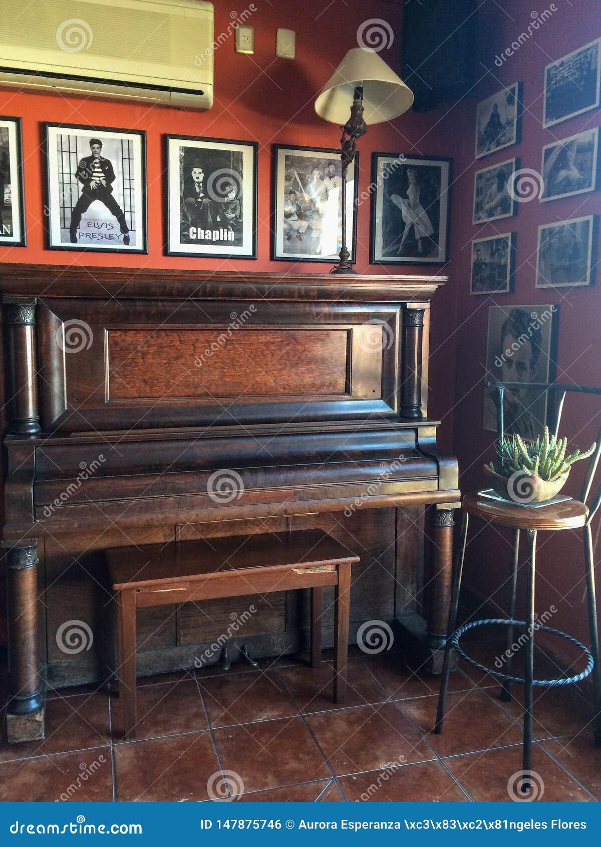Piano e fotografias velhos de cantores e de atores famosos