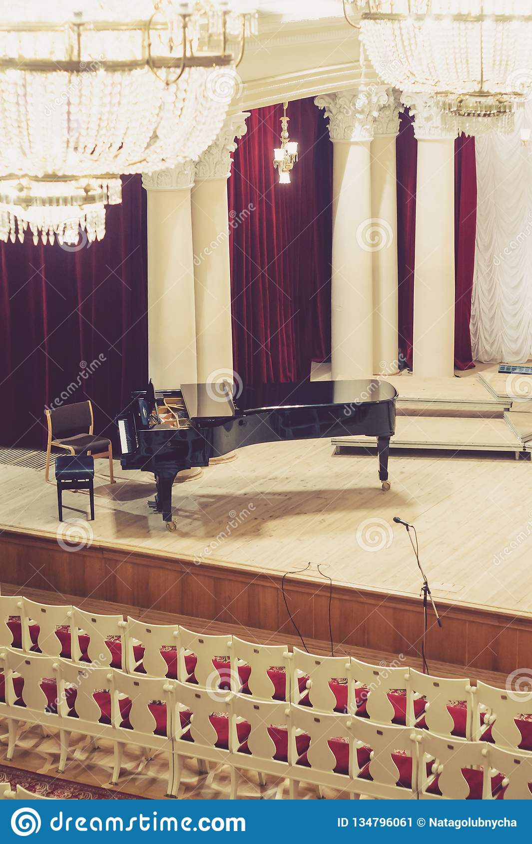 Piano on scene and empty chairs in the concert hall