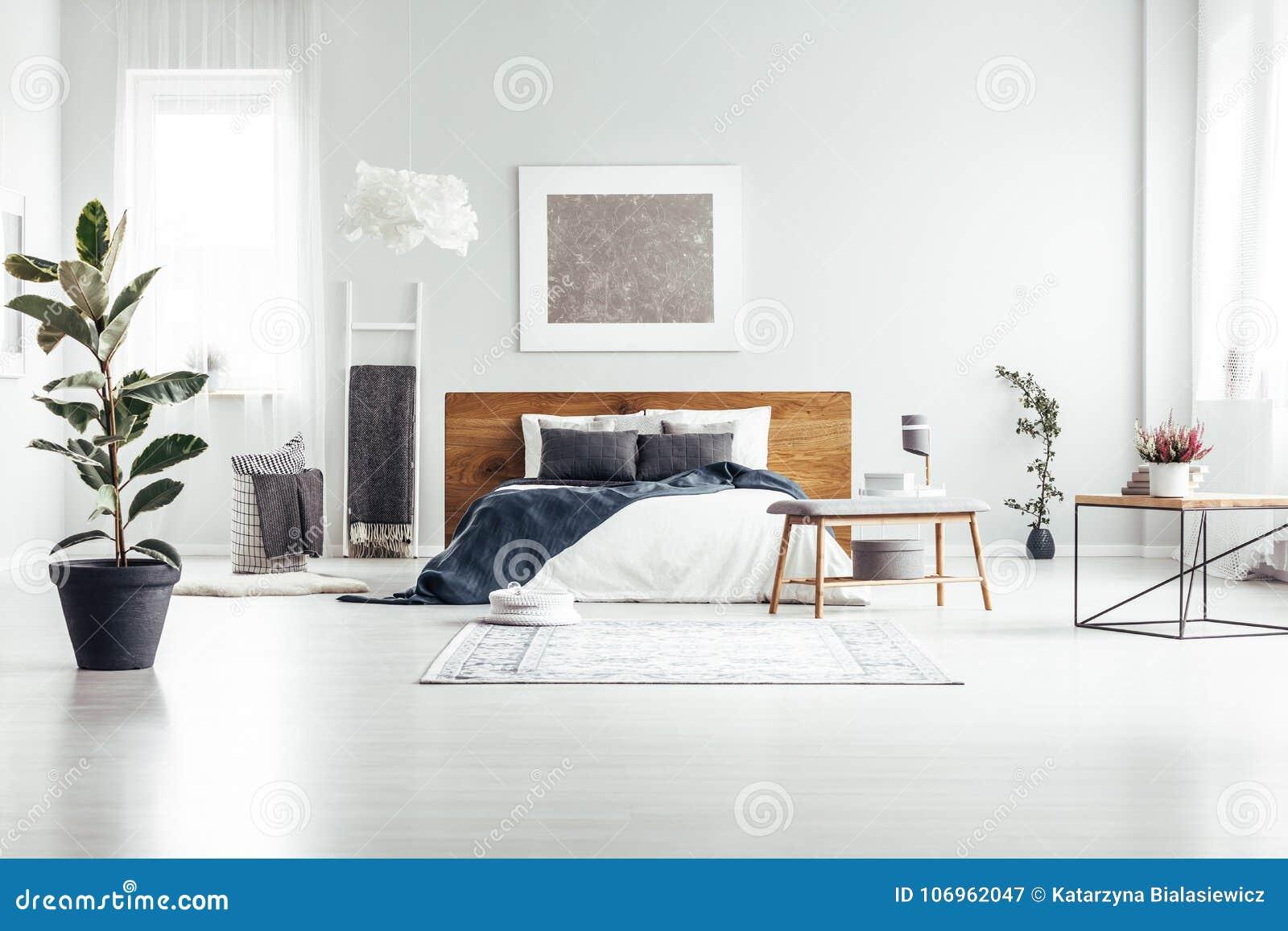 Pianta in camera da letto bianca spaziosa immagine stock