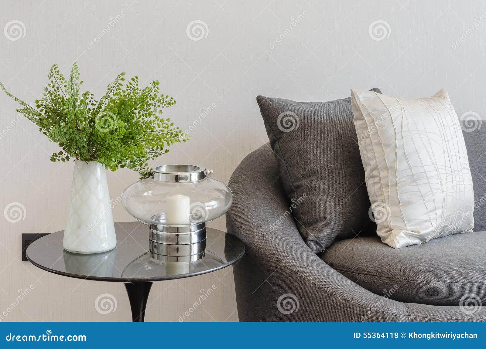 Pianta in vaso bianco sulla tavola rotonda con il sofà ed i cuscini