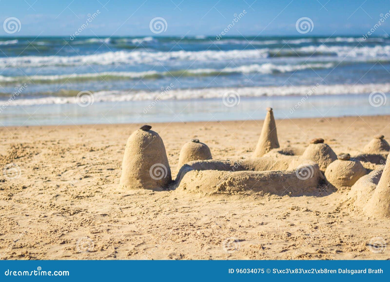 Piaska kasztel na plaży z tocznymi fala w tle