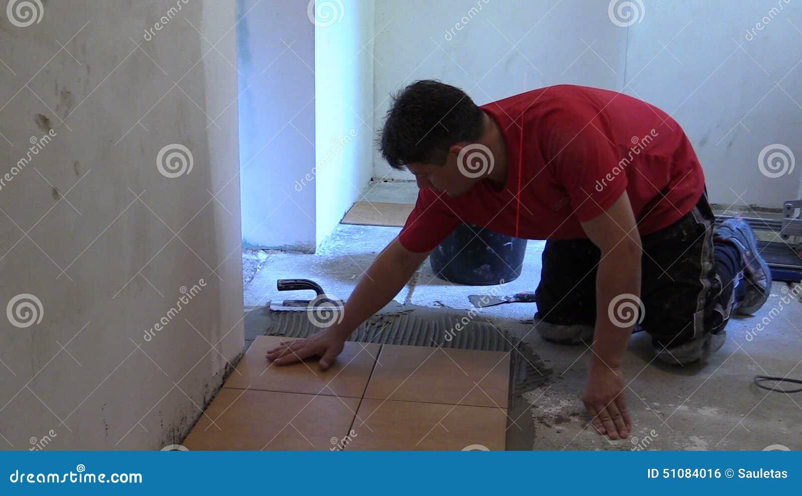Piastrella di ceramica della colla dell uomo sul pavimento della