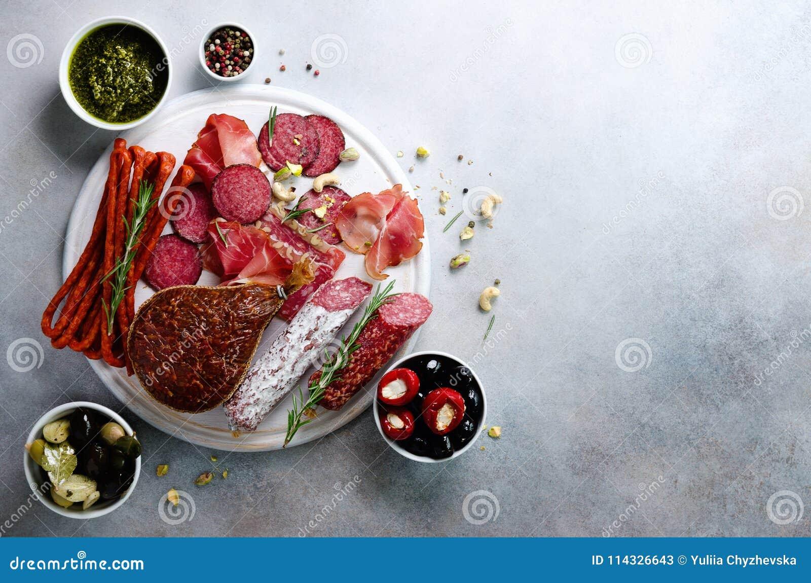 Piatto affumicato freddo della carne Antipasto italiano tradizionale, tagliere con salame, prosciutto di Parma, prosciutto, braci