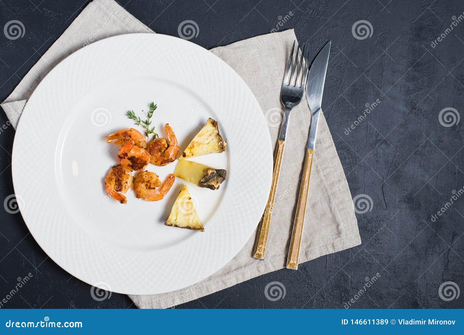 Piatto bianco con i gamberetti di re e le fette fritti dell ananas