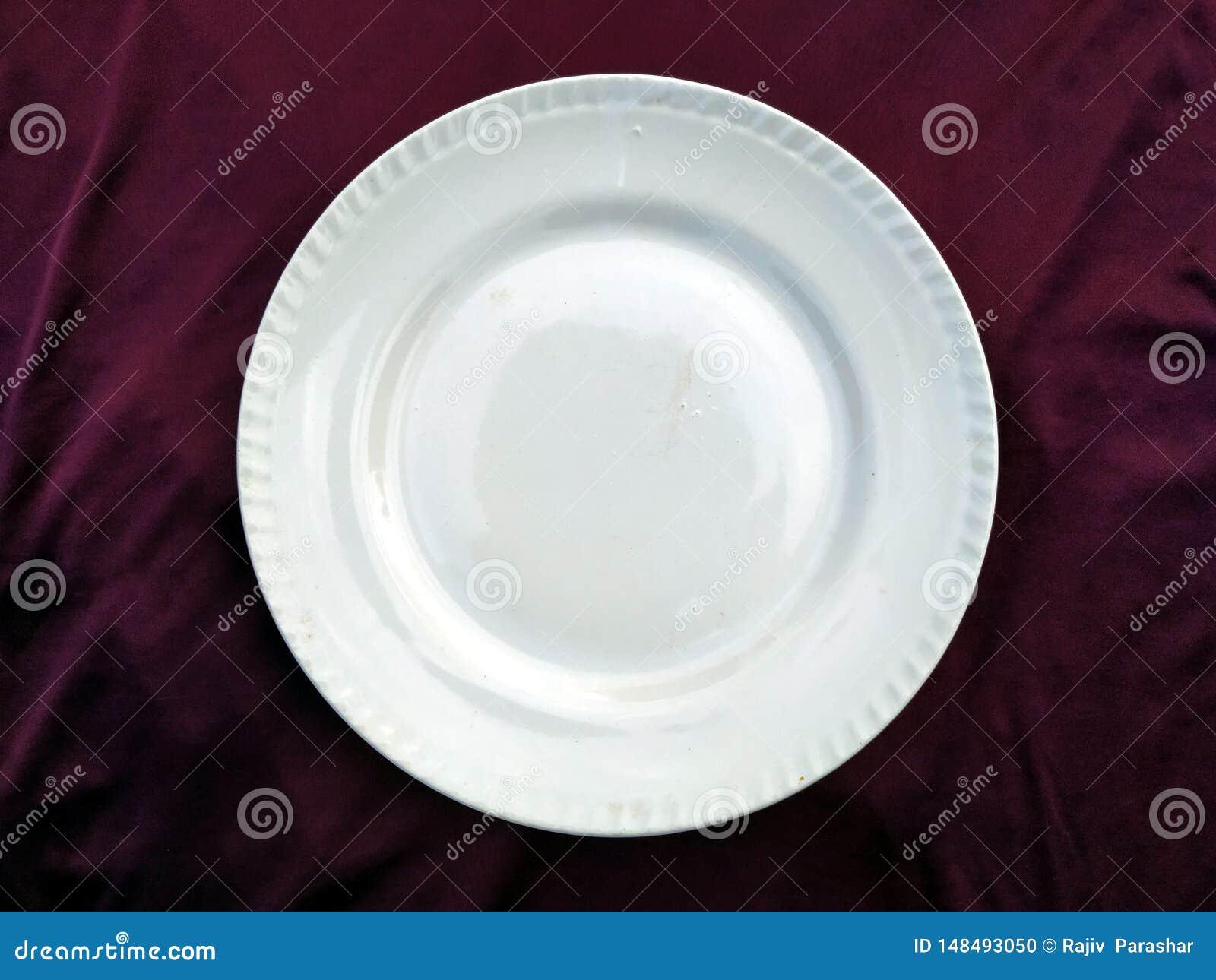Piatto bianco vuoto isolato su un fondo viola