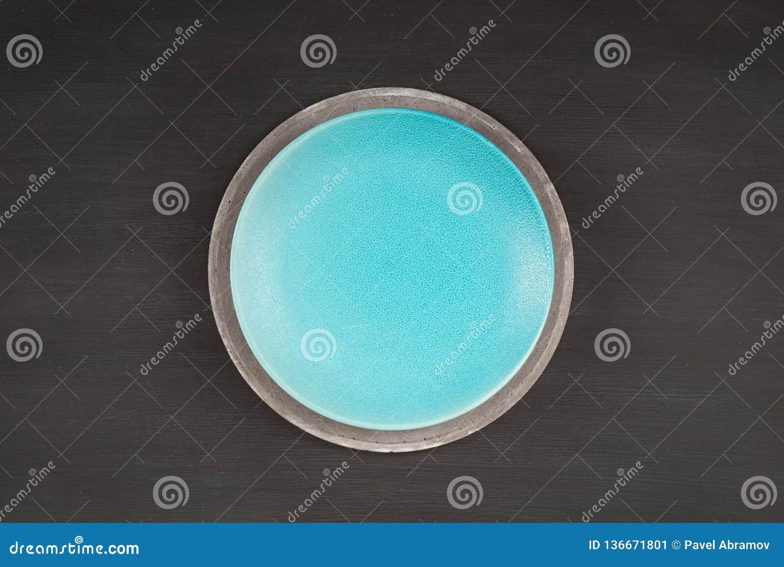 Piatto blu sul piatto concreto su fondo scuro