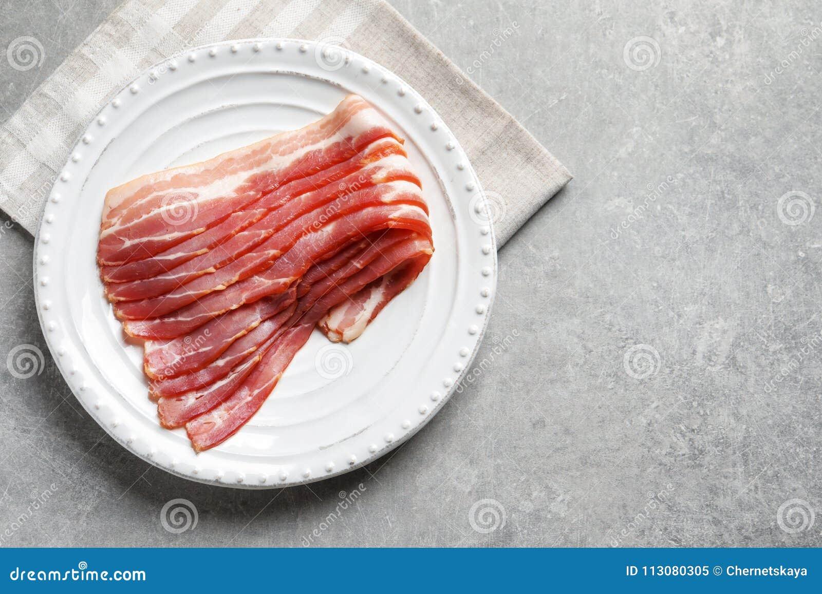 Piatto con le fette di lardo crude del bacon