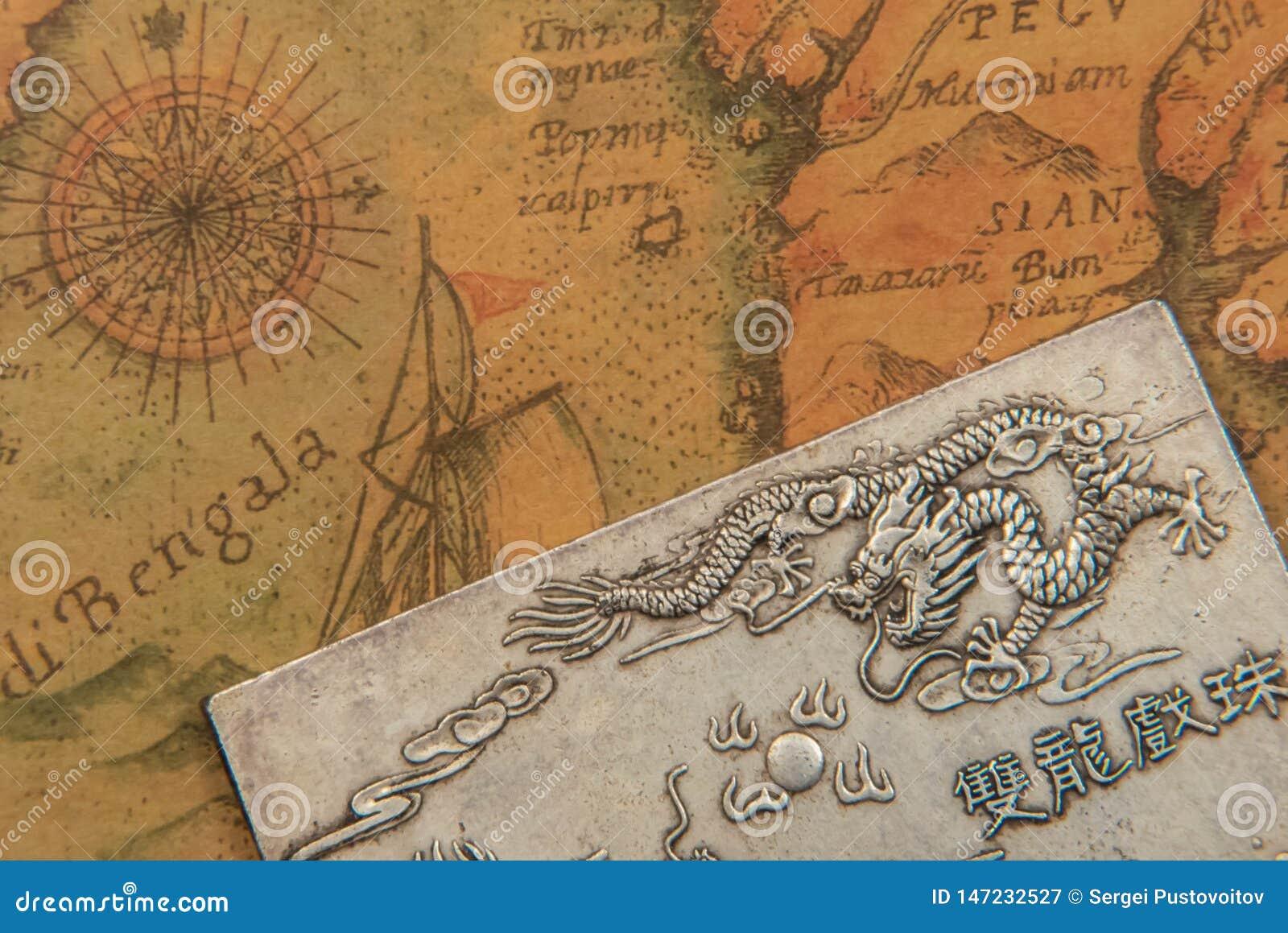 Piatto d argento antico con i draghi combattenti sulla mappa di mondo stile orientale antica