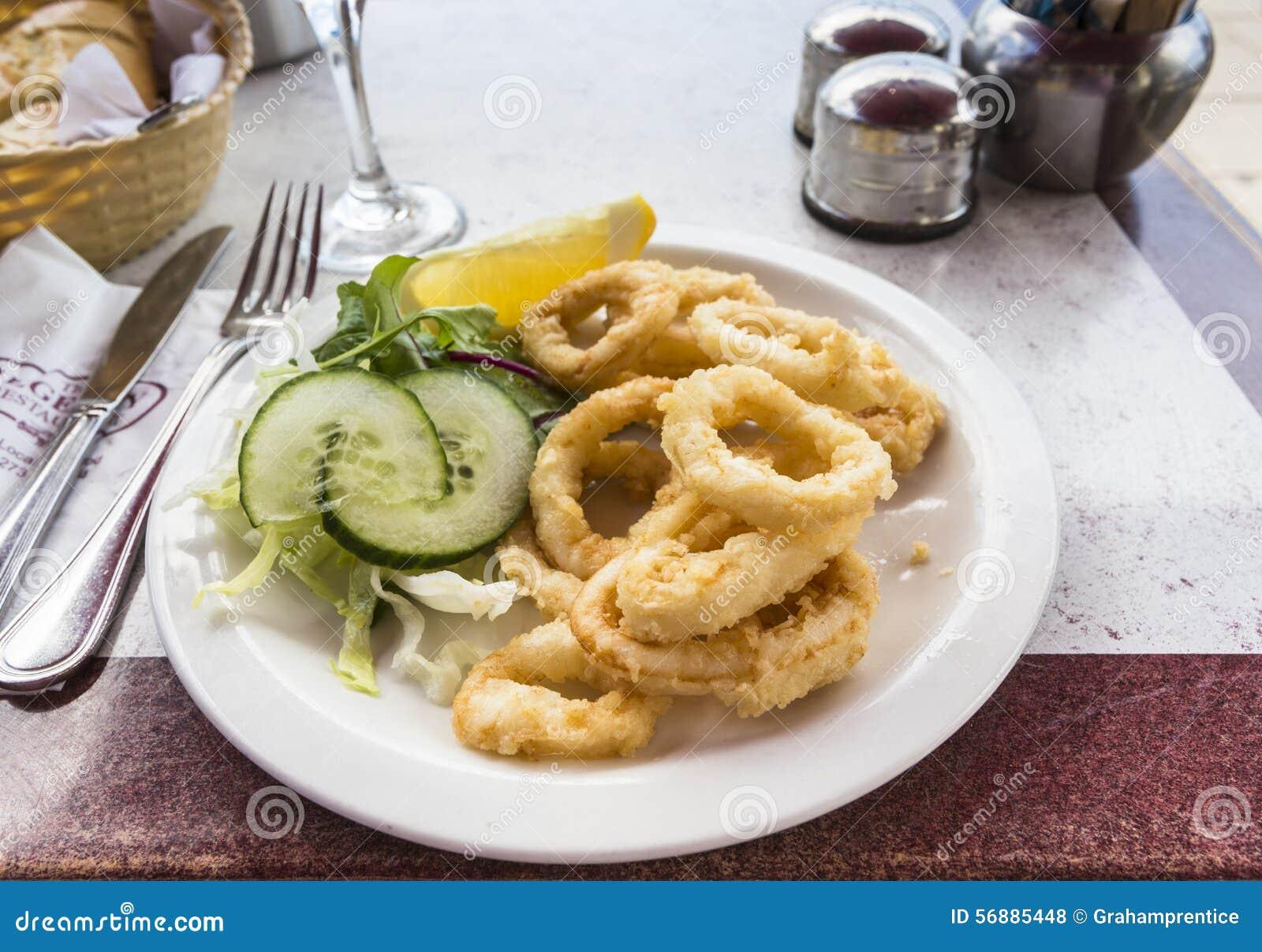 Piatto dei calamari fritti (anelli del calamaro) con il contorno di insalata