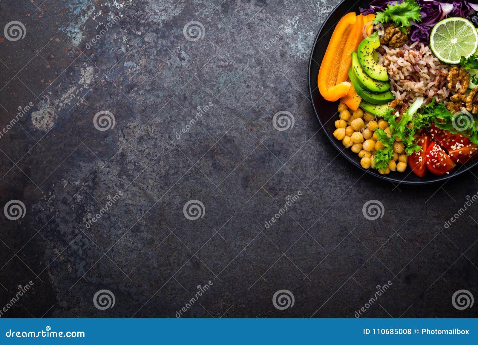 Piatto della ciotola di Buddha con riso sbramato, l avocado, il pepe, il pomodoro, il cetriolo, il cavolo rosso, il cece, l insal