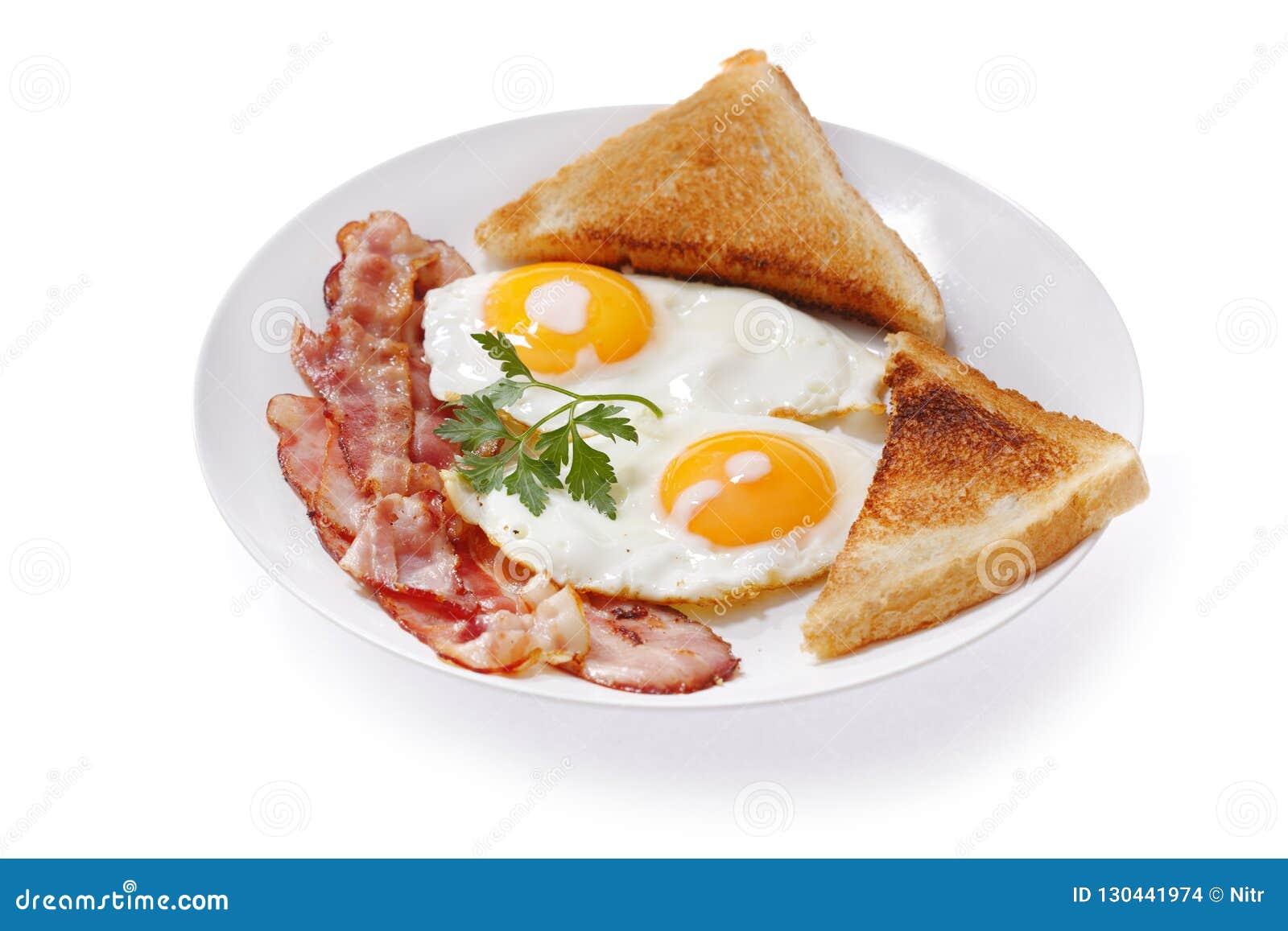Piatto delle uova fritte, del bacon e del pane tostato su fondo bianco
