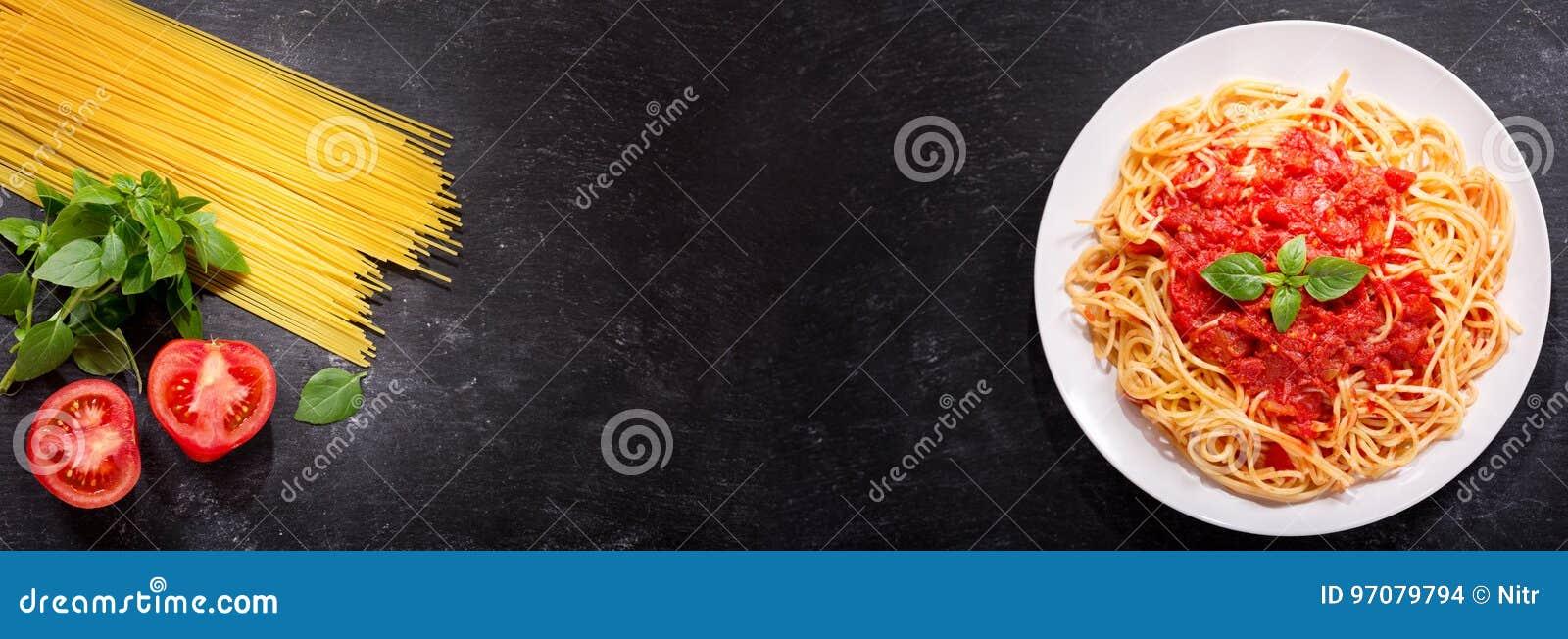 Piatto di pasta con salsa al pomodoro e gli ingredienti per cucinare