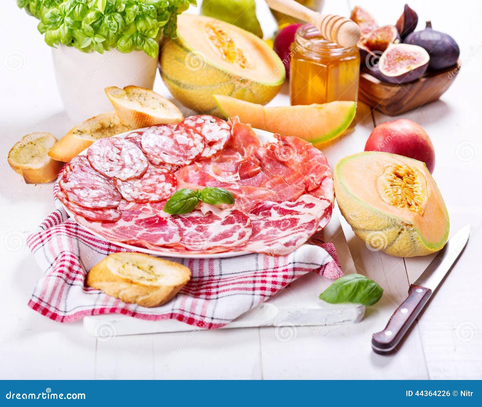 Piatto di vari prosciutto e salame con la frutta fresca