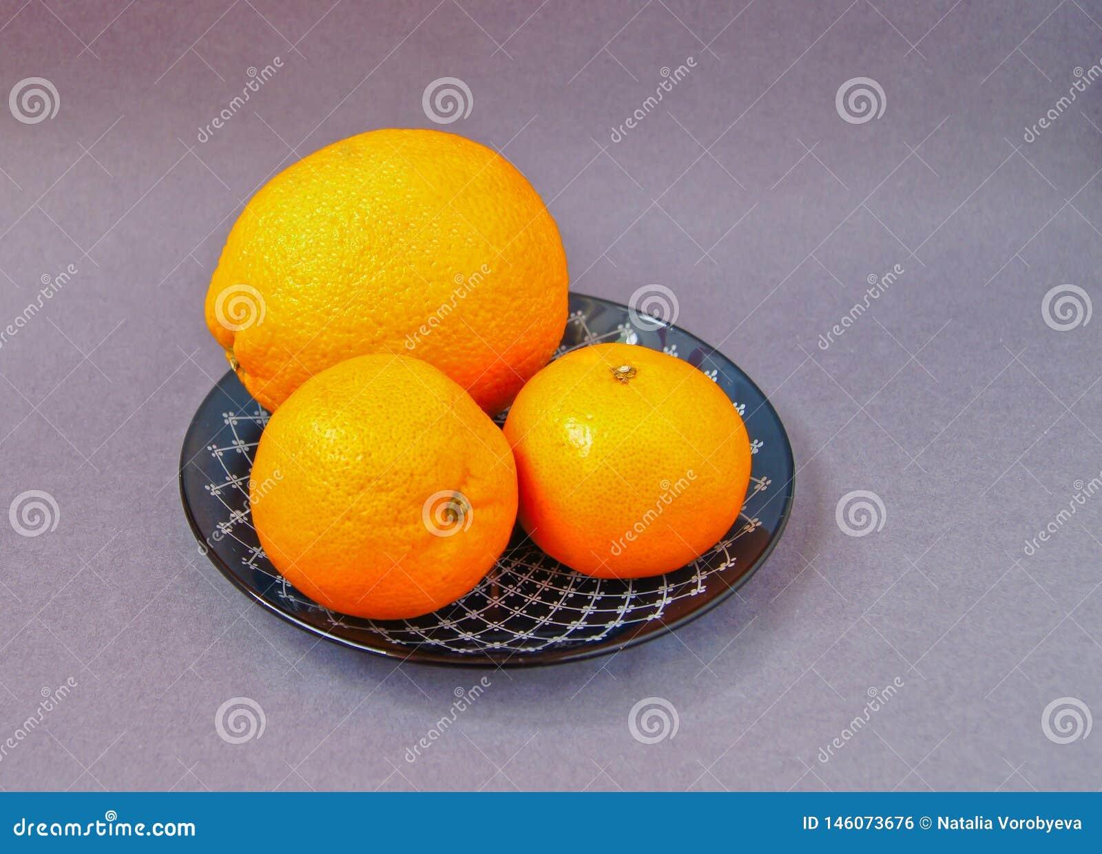 Piatto rosso con le arance e la bottiglia delle foglie verdi dei mandarini con succo su fondo leggero Spazio della copia di vista