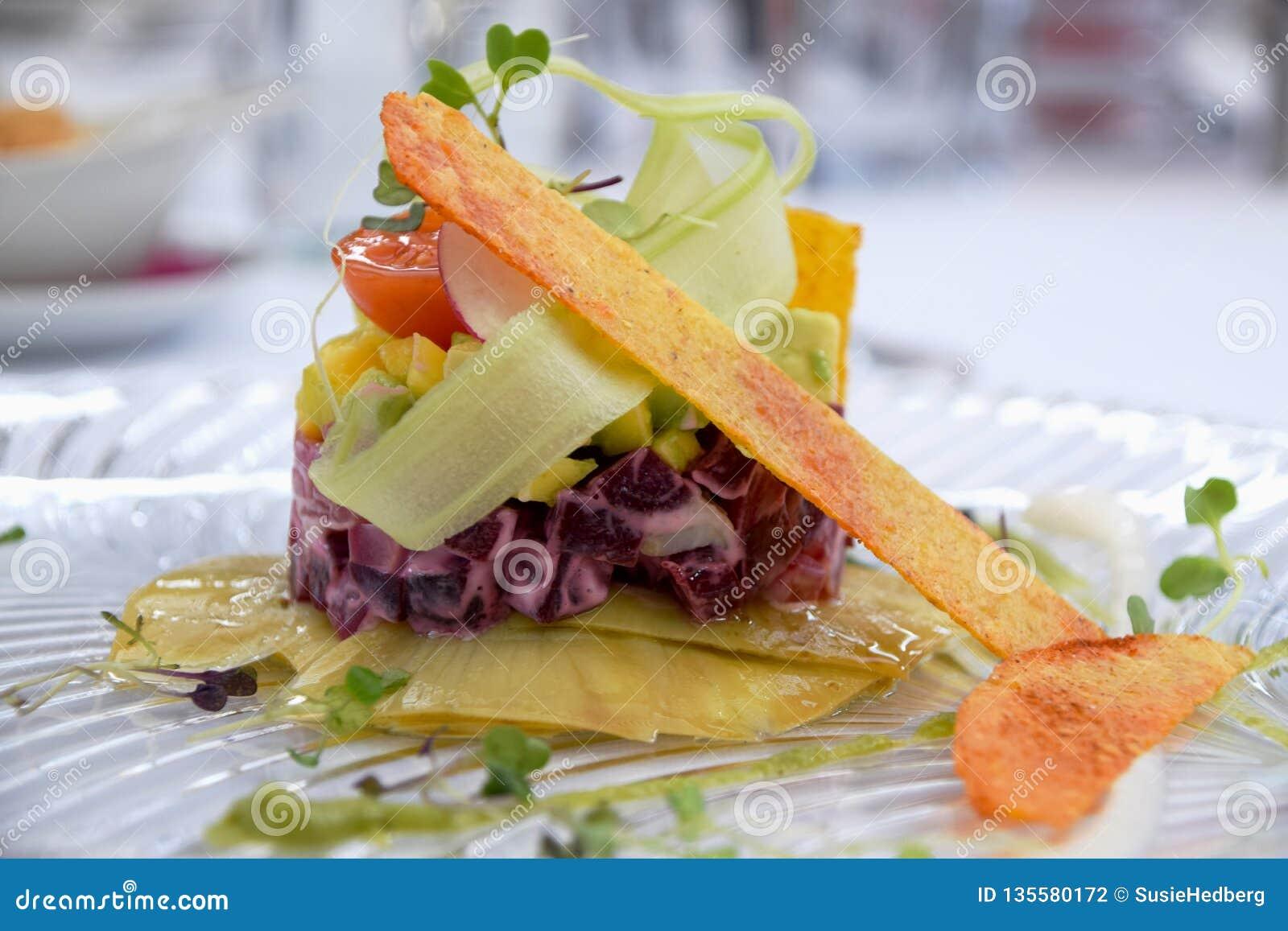 Piatto vegetariano del tartaro con barbabietola, mais, l avocado, i pomodori e gli ortaggi a radici