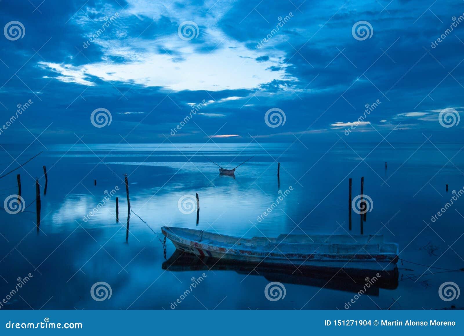 Piccola barca ed il tramonto blu in Campeche Messico