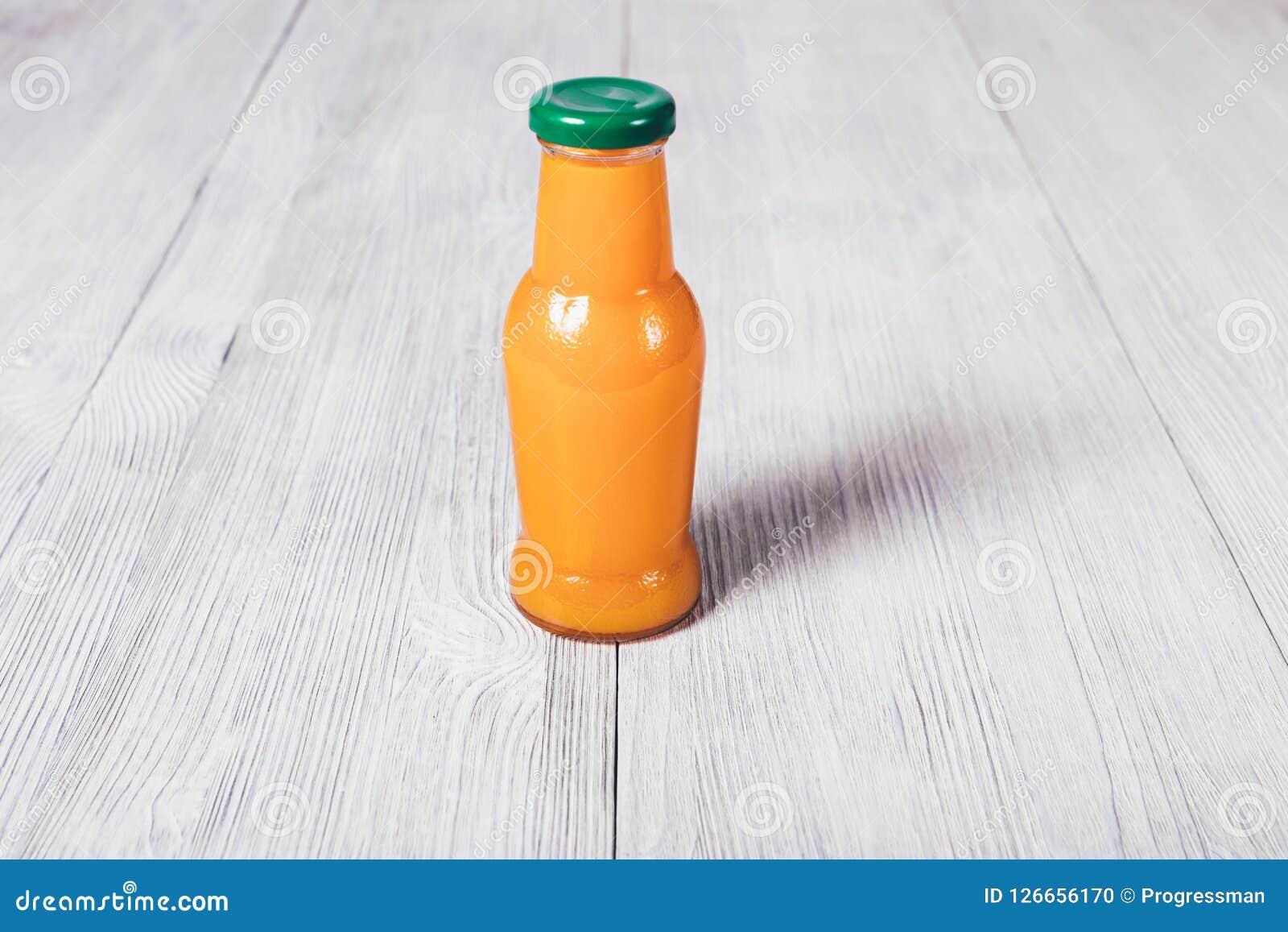 Piccola bottiglia dei supporti del succo d arancia sulla tavola di legno bianca