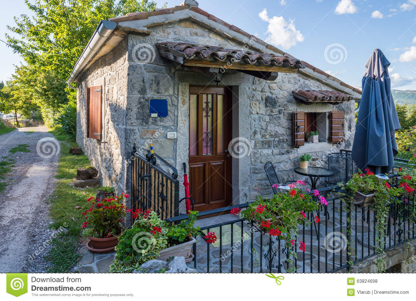piccola casa di pietra con un recinto del metallo