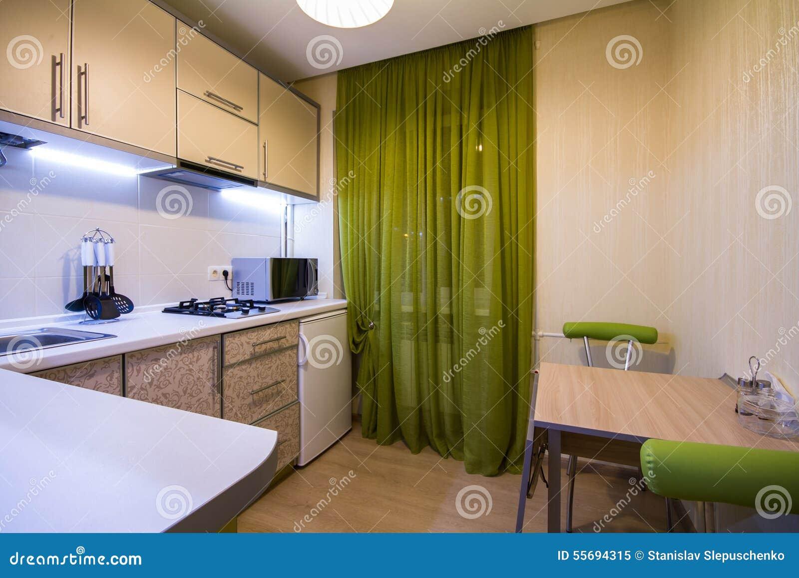 Piccola cucina moderna con le tende verdi immagine stock