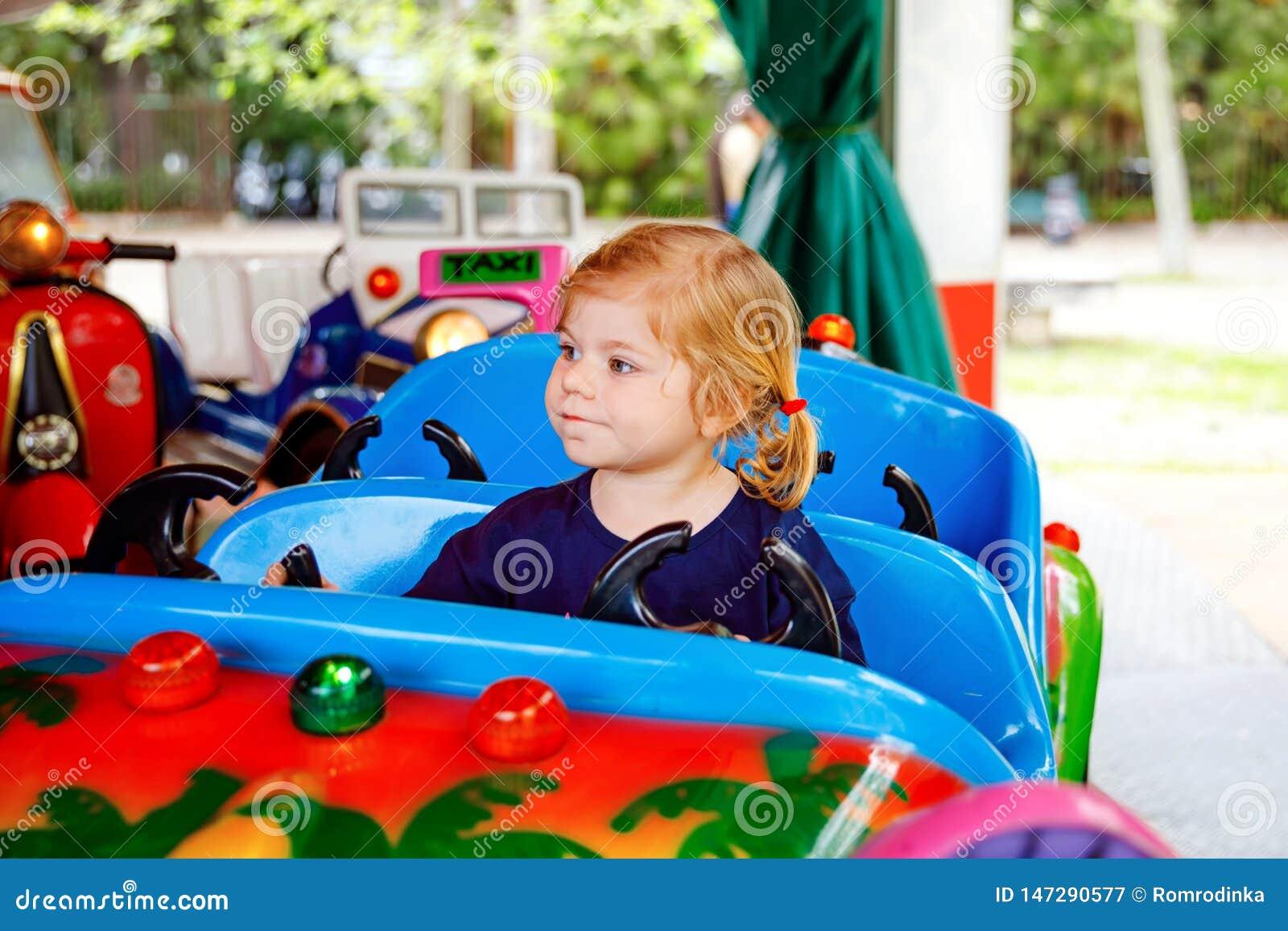 Piccola guida adorabile della ragazza del bambino sull automobile divertente sul carosello della rotonda in parco di divertimenti