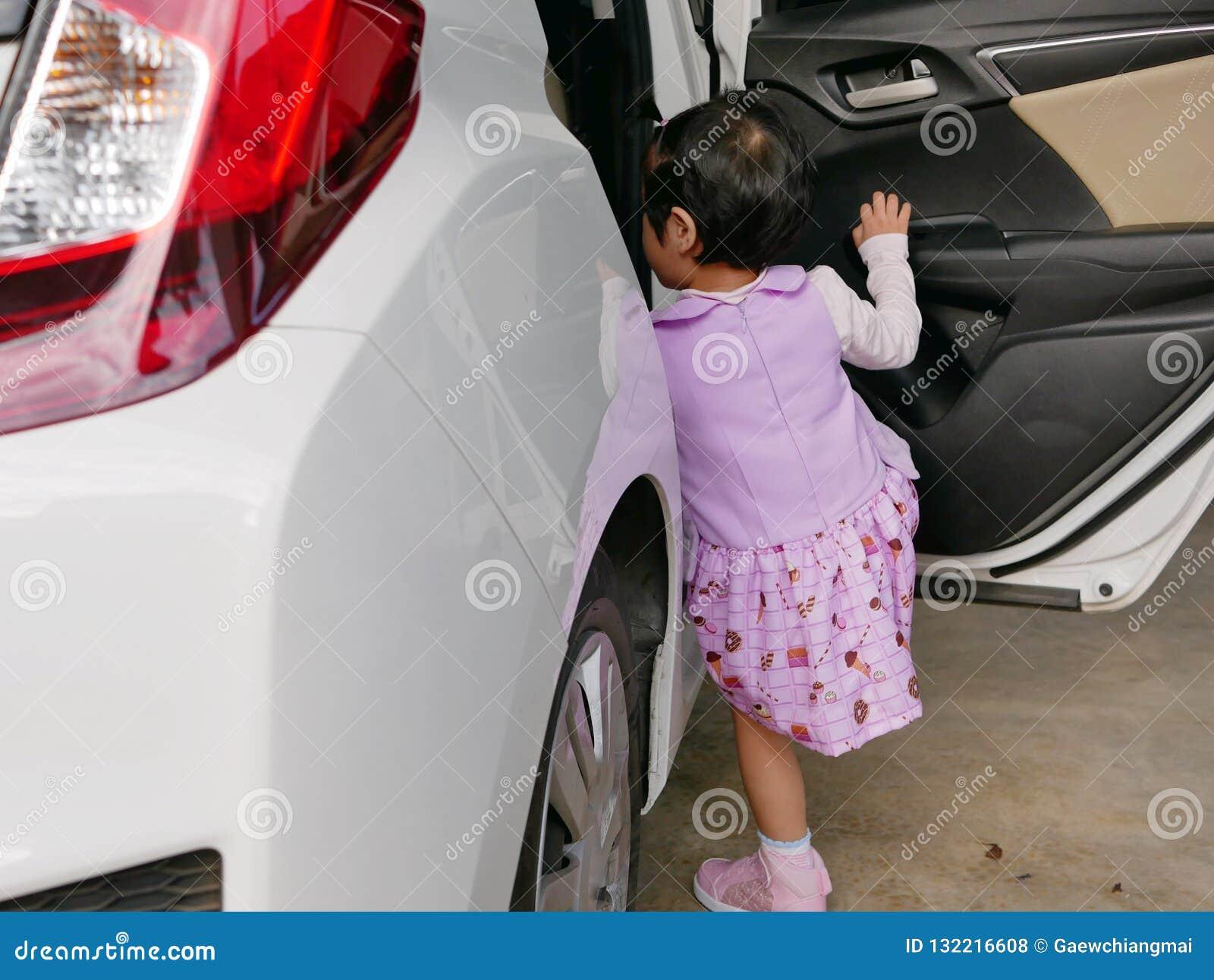 Piccola neonata asiatica che impara entrare nell automobile sola