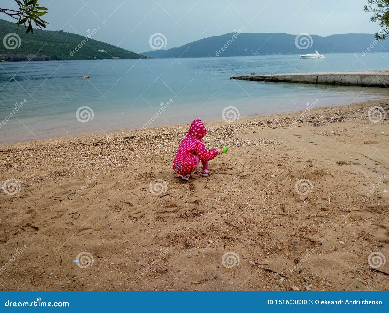 Piccola neonata sveglia che gioca con la sabbia alla spiaggia in un tempo tempestoso