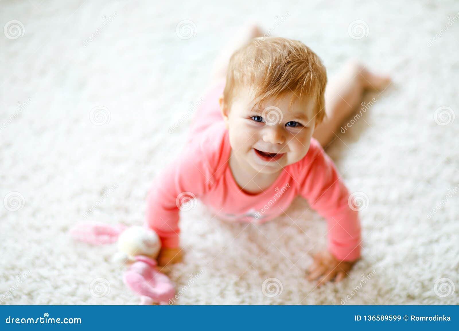 Piccola neonata sveglia che impara strisciare Bambino in buona salute che striscia nella stanza dei bambini con i giocattoli vari