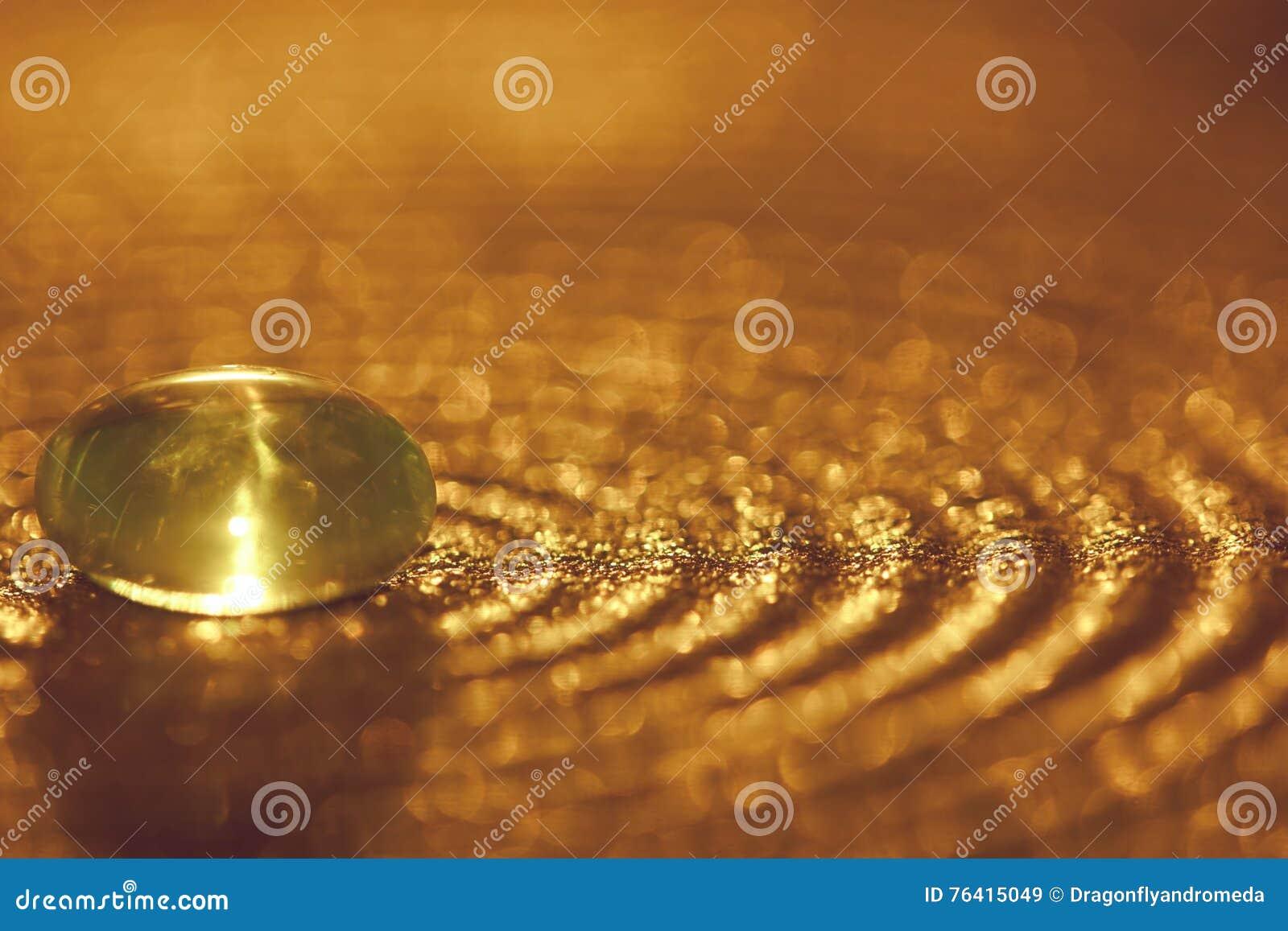 Piccola pietra di vetro su un piatto con le scintille e il bokeh dorati