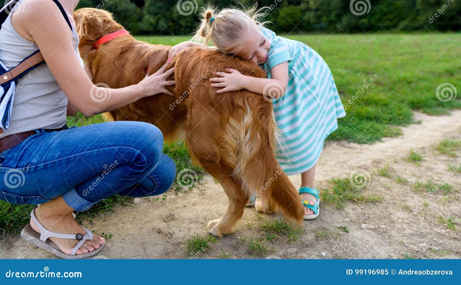 Piccola ragazza bionda che sorride e che abbraccia il suo golden retriever sveglio del cane di animale domestico